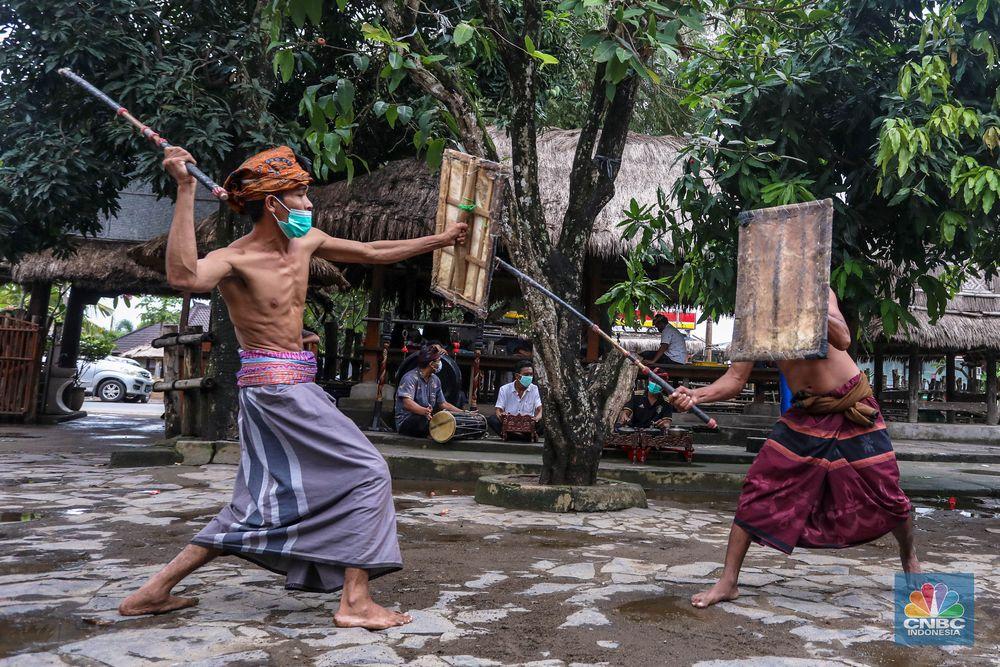 Dua orang petarung memperagakan kesenian khas yang dimiliki masyarakat Lombok, Presean. Seni tradisi ini dilakukan dengan cara adu ketangkasan.  Peresean adalah pertarungan antara dua lelaki yang bersenjatakan tongkat rotan (penjalin) dan berperisai kulit kerbau yang tebal dan keras (perisai disebut ende). Tradisi ini dilakukan oleh masyarakat suku Sasak.  Tradisi ini dilakukan dengan menggunakan penjalin, terbuat dari rotan yang dibaluri aspal hitam dan di dalamnya terdapat pecahan beling yang diikat dengan benang bola warna putih. Penjalin digunakan sebagai alat untuk saling memukul. Ukuran panjangnya sekitar 1,5 meter. (CNBC Indonesia/ Andrean Kristianto)