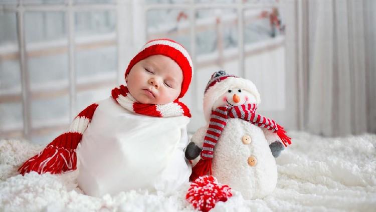 Christmas portrait of cute little newborn baby boy, wearing santa hat and  little cute snowman toy, studio shot, winter time