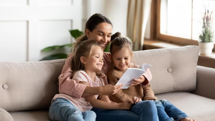 Happy family young mother babysitter hold read book relax embrace cute little children daughters, smiling parent mum tell small kids funny fairy tale story sit on sofa having fun together at home