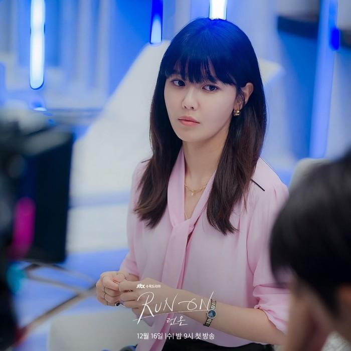 Lepas dari blazer. Seo Dan Ah tampil kasual dengan blouse merah muda dengan model ikatan seperti dasi di bagian depannya. Dia pun menggulung bagian lengan hingga ke siku. Dia tetap masih menambahkan aksesoris kalung dan anting, tetap menambahkan jam pada bagian lengannya.(Foto:Instagram/jtbcdrama)