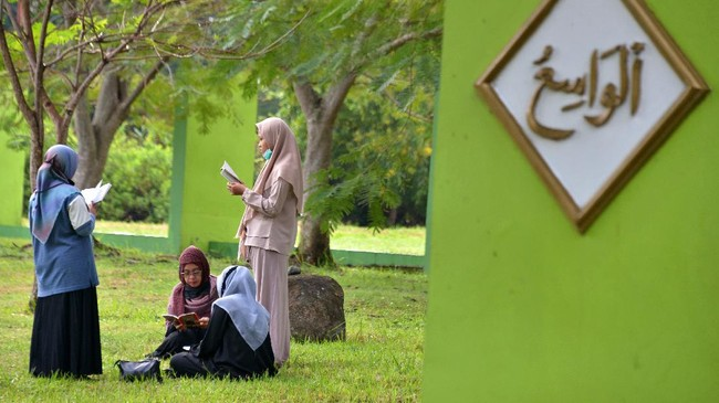 Keluarga menggelar ziarah kubur di pemakaman massal korban tsunami Aceh. Bencana tersebut merenggur korban tewas hingga ratusan ribu orang.