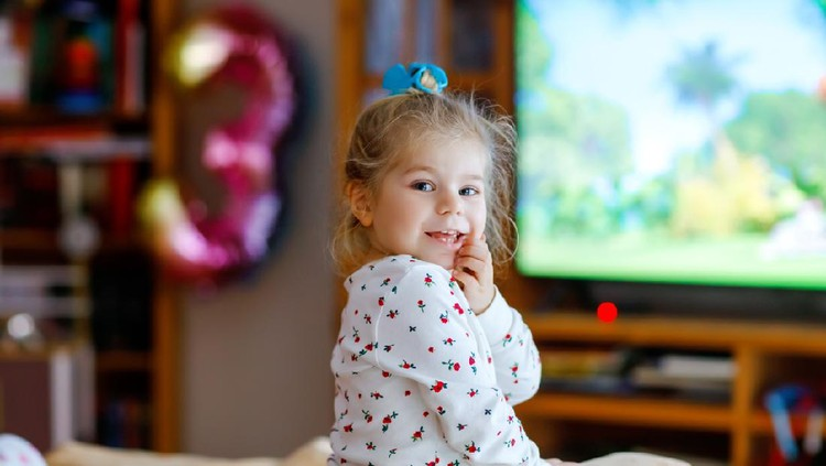 Cute little toddler girl in nightwear pajamas watching cartoons or movie on tv. Happy healthy baby child at home