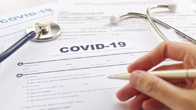 COVID-19 Health insurance concept. Blurring of hand holding pen and Stethoscope on health form. Focus on