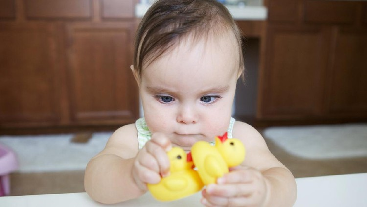 A cute Asian/Eurasian baby girl is fixated on a hanging mobile toy. Her eyes are slightly crossed as she examines it. She is just over 1 years old.