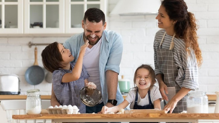 Overjoyed young family with little preschooler kids have fun cooking baking pastry or pie at home together, happy smiling parents enjoy weekend play with small children doing bakery cooking in kitchen