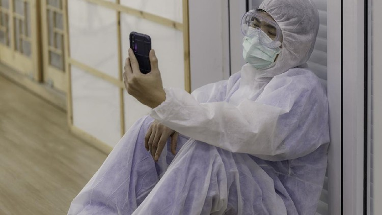 young Asian doctor, dressed in anti-virus clothing, sits on the floor tired and uses a smartphone to make a video call to his family. corona virus concept.