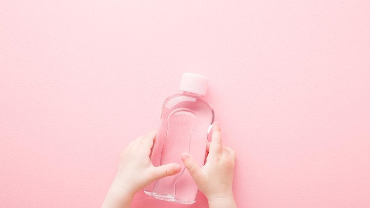 Baby girl little hands holding transparent plastic bottle of oil on light pink table background. Pastel color. Care about soft body skin. Closeup. Point of view shot. Top down view.