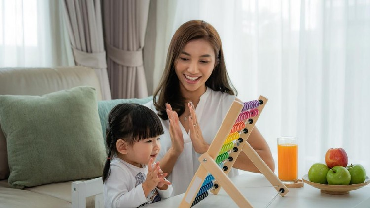 Happy Asian young mother and daughter playing with abacus, early education at home.