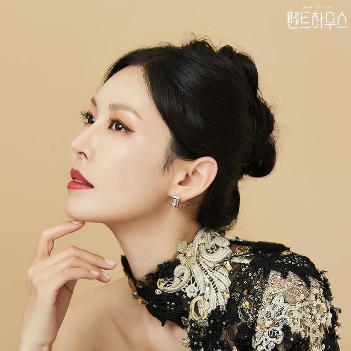 Pemakaian lipstik merah mempertegas penampilan tokoh Cheon Seo Jin yang diperankan Kim So Yeon. Dengan padu padan half shoulder dress berwarna hitam dengan brukat krem selaras dengan warna rambutnya yang hitam. Model rambut disanggul dan potret dari samping makin mempertegas wajahnya (Foto: Instagram.com/sbsdrama)
