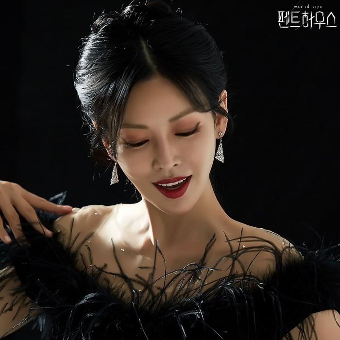 Hitam seolah menjadi paten potret tegas tokoh Cheon Seo Jin saat memakai lipstik merah. Kali ini, terpotret dengan off shoulder dress dengan hiasan bulu halus mengikuti bagian shoulder. Anting berbentuk segitiga dan sanggul membuatnya tampak makin elegan.(Foto: Instagram.com/sbsdrama)