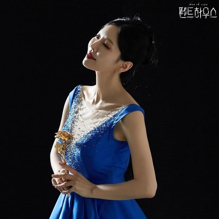 Beralih dari warna hitam, tokoh Cheon Seo Jin kini tampil dengan long sleeve dress warna biru. Meski tetap tampil dengan lipstik merah, tampilannya kini tak membawa aura arogan atau antagonis. Dirinya tampak manis ditambah senyum tipis dan setangkai bunga yang dipegangnya.(Foto: Instagram.com/sbsdrama)