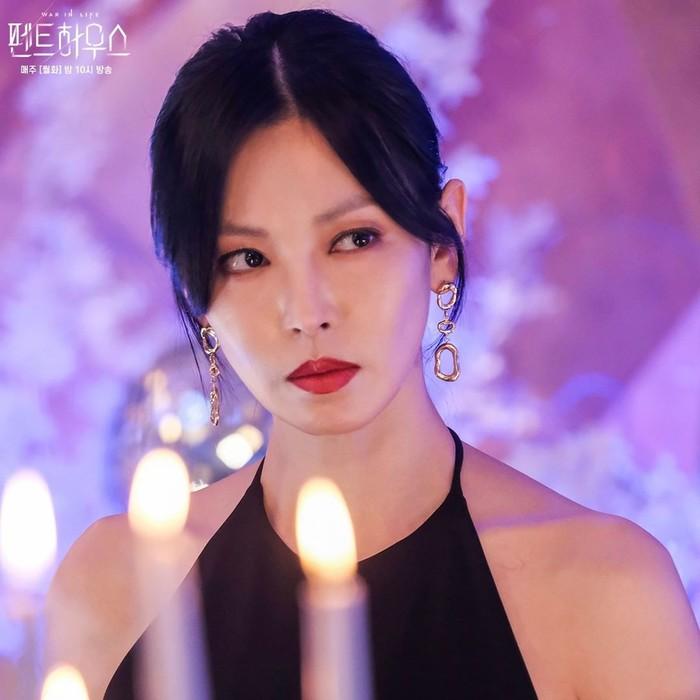 Balik lagi ke karakter dalam adegan Cheon Seo Jin. Buat para penonton drakor ini pasti ingat potret adegan ini. Yak, ini saat So Jin hadir dalam pesta bersama Hera Palace Club saat menjamu tamu Logan Lee. Ia kembali dengan setelan dress hitam, dengan rambut sanggul, anting dan lipstik merah andalannya.(Foto: Instagram.com/sbsdrama)
