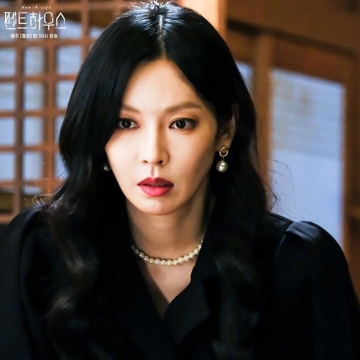 Kali ini, tokoh Cheon Seo Jin hadir menggerai rambutnya, tak lagi disanggul. Meski hadir dengan dress hitam dan rambut hitam yang digerai, warna lipstik merah seolah mempertegas penampilannya. Ditambah, kalung dan anting bola mutiara.(Foto: Instagram.com/sbsdrama)