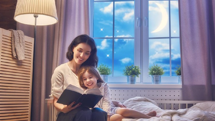 Father reading a book to his daughter while lying on the floor in bedroom