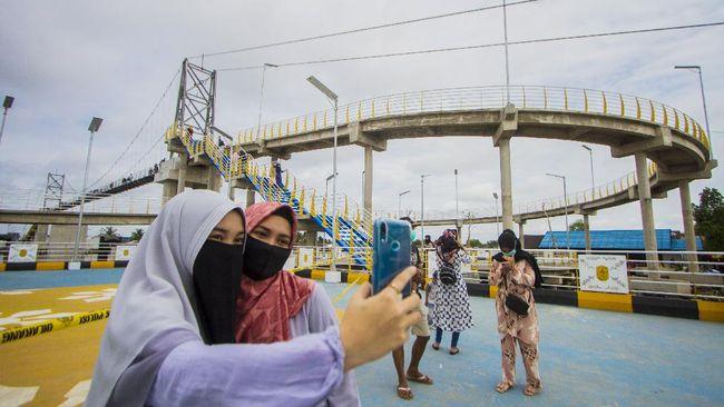 Di atas Sungai Martapura, Banjarmasin Selatan, kini berdiri jembatan yang bentuknya melingkar mirip wahana permaianan roller coaster.