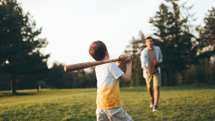 Young father sharing basics of baseball with his little boy, outdoors in the park