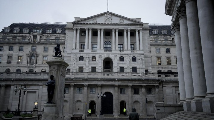 A man walks backdropped by the Bank of England in the City of London financial district in London, Jan. 5, 2021, on the first morning of England entering a third national lockdown since the coronavirus outbreak began. British Prime Minister Boris Johnson on Monday night announced a tough new stay-at-home order that will last at least six weeks, as authorities struggle to stem a surge in COVID-19 infections that threatens to overwhelm hospitals around the U.K. (AP Photo/Matt Dunham)