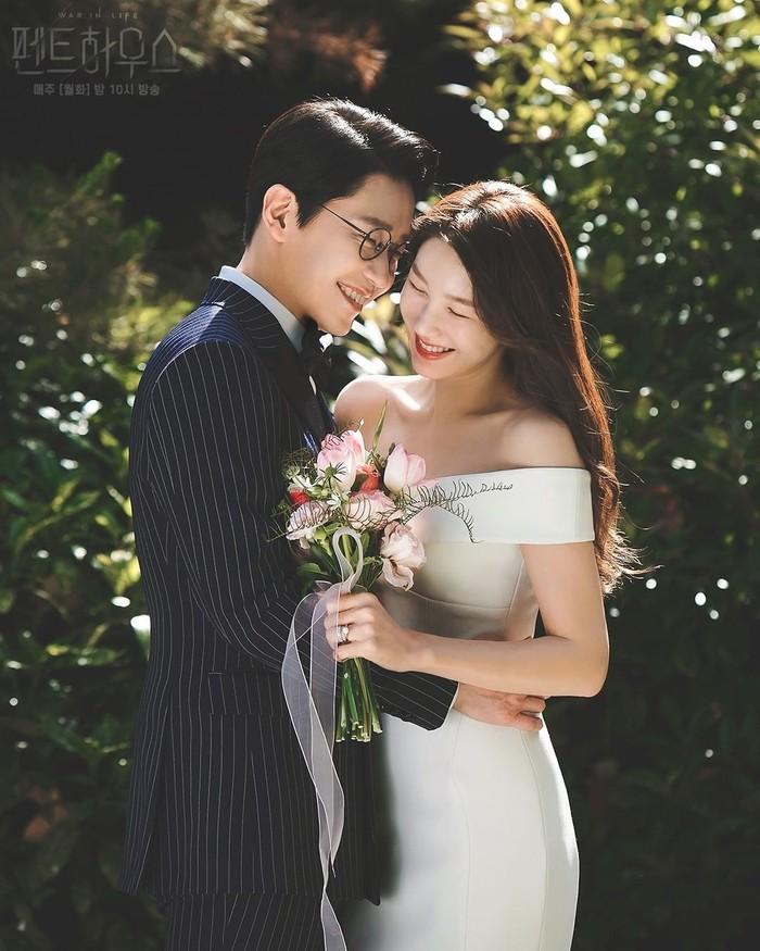 Kini giliran potret keluarga pasangan menikah tokoh Joo Dan Tae (Uhm Ki Joon) dan Shim So Ryeon (Lee Ji Ah) yang memamerkan potret mesra. Lengan yang melingkar di pinggang So Ryeon dan tatapan mesra ke arah wajah menjadi pilihan untuk potret romantis bersama istri.Sumber/Instagram/sbsdrama.official.