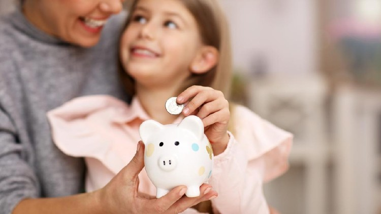 Picture of young girl and her mother with piggybank sitting at table