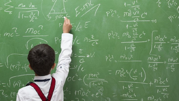 Little professor solving math problem on blackboard