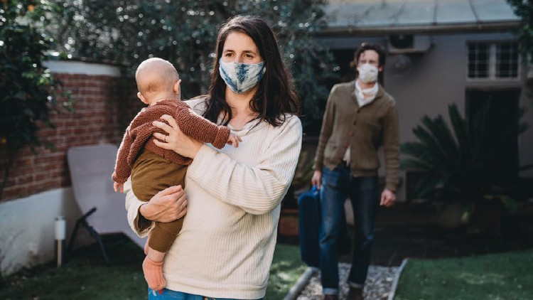 Family with one child traveling during Covid-19, wearing protective face masks. They are arriving at a bed and breakfast.