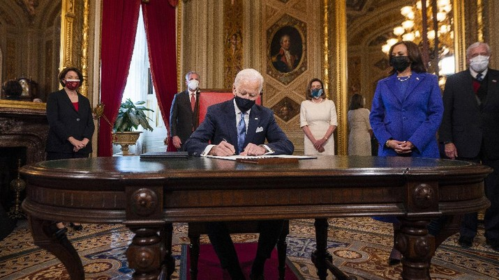 President Joe Biden signs three documents including an inauguration declaration, cabinet nominations and sub-cabinet nominations in the President's Room at the US Capitol after the inauguration ceremony, Wednesday, Jan. 20, 2021, at the U.S. Capitol in Washington. Vice President Kamala Harris watches at right. (Jim Lo Scalzo/Pool Photo via AP)
