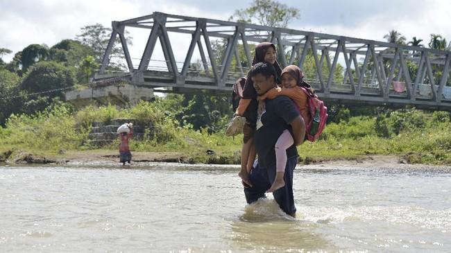 Warga dan siswa sekolah di Desa Panca, Kecamatan Lembah Seulawah, Aceh Besar, harus berjuang menyeberangi sungai sejak jembatan gantung terputus pada 2004.
