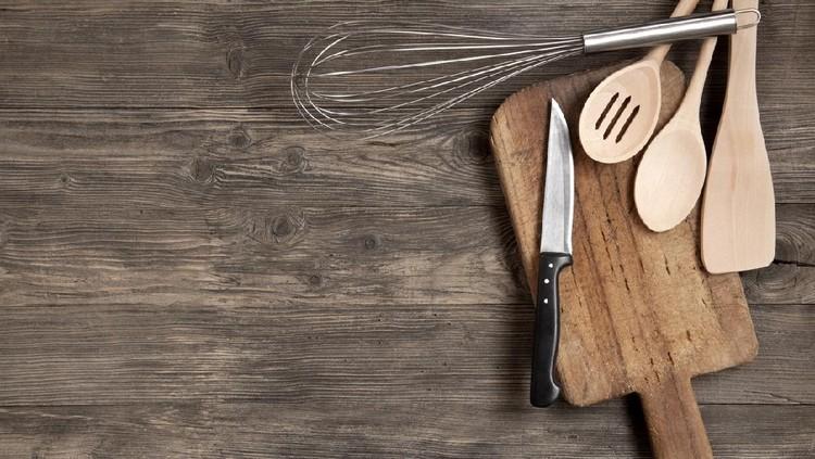 Kitchen utensils on an old wooden background
