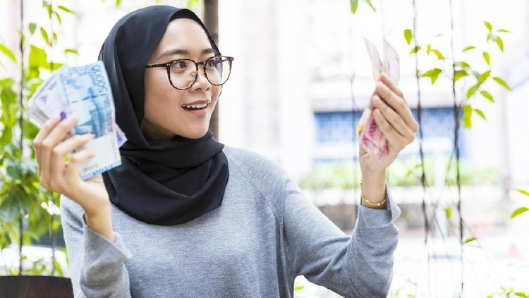 Malaysian Girl wearing hijab, rejoicing her first salary and counting cash, woman money