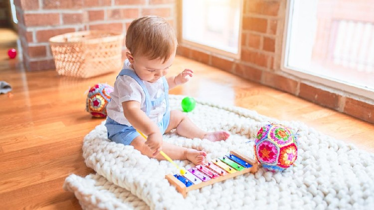 Beautiful toddler sitting on the blanket playing xylophone smiling at kindergarten