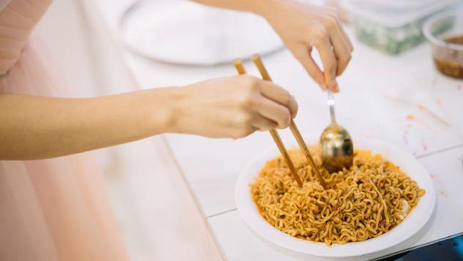 Seorang wanita meracik mi goreng instan dengan tambahan emas (edible gold) 24 karat. Edible gold sendiri biasa digunakan sebagai bahan dekorasi makanan.
