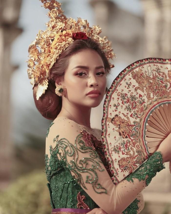Aurelie tampak anggun dengan pakaian tradisional Bali yang cerah dengan warna hijau. Dia memakai kebaya lengkap dengan sanggul Pusung Tagel, dan aksesoris kepala Payas serta kipas/Sumber/Instagram/aurelie.hermansyah.