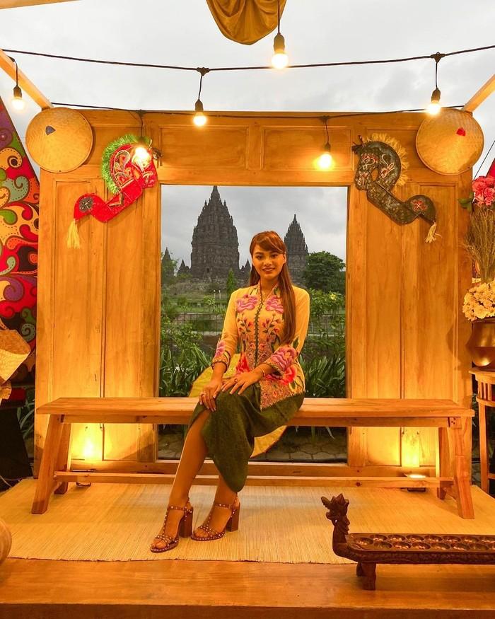 Saat berlibur ke Prambanan, Jawa Tengah, Aurelie juga memakai pakaian tradisional setempat dengan kebaya modern. Dia tampil dengan paduan kebaya warna hijau-kuning yang dipadu dengan heels, serta rambut digerai/Sumber/Instagram/aurelie.hermansyah.