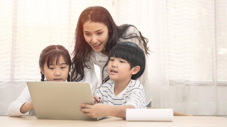 Happy young Asian family with children and their mother using computer do school homework at home.