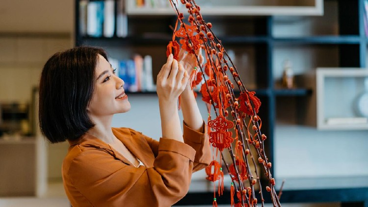 Image of an Asian Chinese woman hanging decoration on a plant and prepare for Chinese New Year