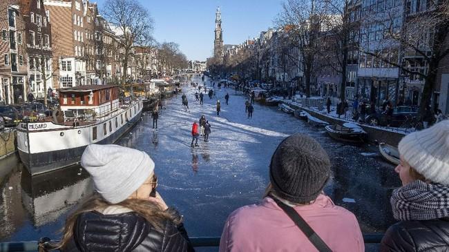 Kanal Prinsengracht di Amsterdam, Belanda, sempat membeku pada pertengah Februari. Warga langsung berdatangan untuk main ice skating.