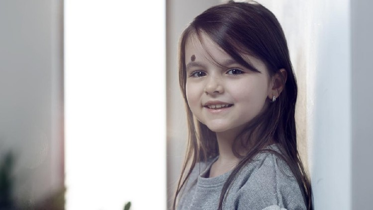 little girl with brown hair smiling indoors,looking at camera.horizontal shot, casual wear.