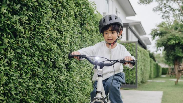 Ilustrasi anak menggunakan helm sepeda