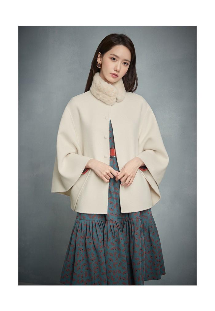 Masih dengan dress bermotif bunga, tetapi kali ini dengan warna motif yang kontras ditambah dengan belt yang warnanya senada dan mantel jubah sebagai outerwear membuat Yoona tampak manis. (Foto: jigott.co.kr)