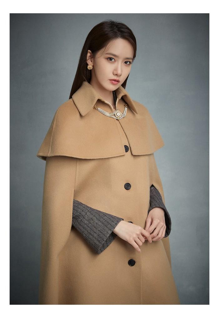 Masih berkonsep winter, Yoona tampil mewah dan elegan dengan gaun wol herringbone dan mantel jubah berwarna coklat. (Foto: jigott.co.kr)