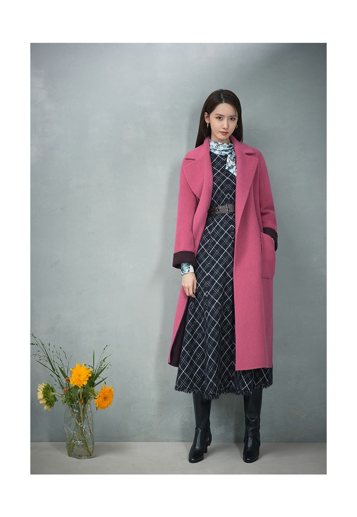 Kali ini Yoona kenakan blouse bermotif daun dan gaun bermotif bordir kotak-kotak, serta mantel bergaya sensasional dengan warna pink. (Foto: jigott.co.kr)