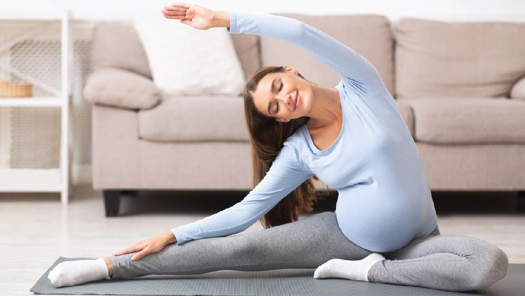 Pregnancy Stretches For Easy Delivery. Pregnant woman doing pilates at home on yoga mat. Copy space