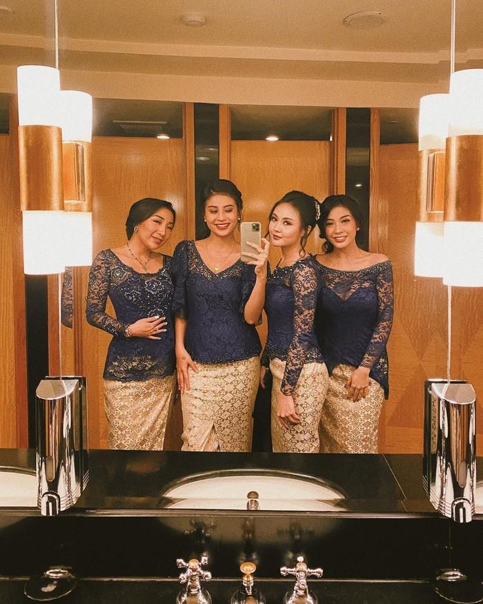 Dipilih sebagai bridesmaid, kamu bisa tampil pakai baju kondangan kembar dengan sahabat dekat seperti Awkarin. Padukan kebaya biru navy model kerah rendah dengan rok songket warna gold (Foto: www.instagram.com/awkarin/).