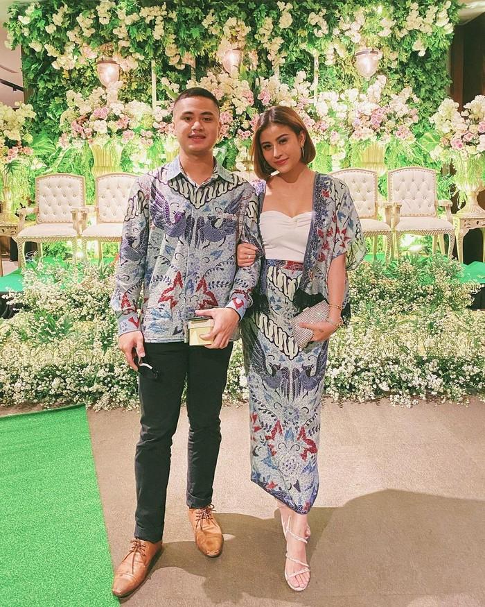 Baju kondangan couple bareng pasangan bisa anti-mainstream dengan meniru outfit ala Awkarin ini, Ladies. Memadukan batik biru sebagai bawahan dengan outer yang diberi inner berbahan satin warna putih (Foto: www.instagram.com/awkarin/).
