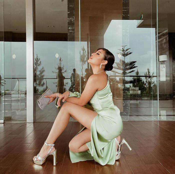 Tampil simpel pakai long dress satin, why not? Meskipun terlihat simpel kamu bisa tetap tampil elegan dengan memilih dress model one-shoulder berwarna hijau. (Foto: www.instagram.com/awkarin/).