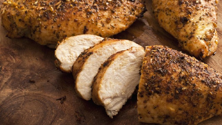Grilled Boneless Chicken breasts, on wood cutting board.