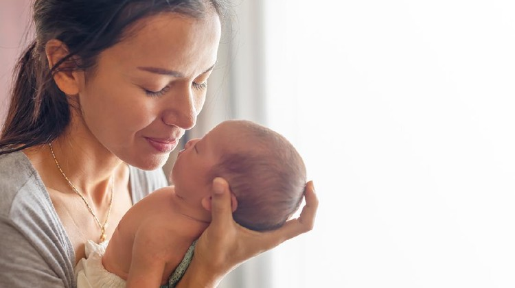 Beautiful mother kissing here little cute baby on her palm. Mother take care her little girl at home. One week newborn girl.