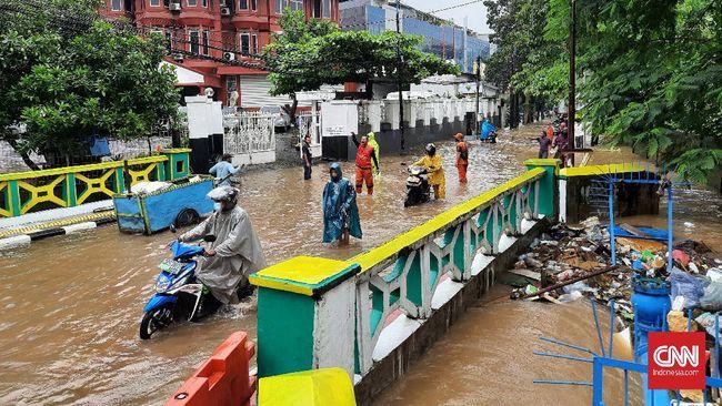 Jalan Pejaten Raya depan pusat perbelanjaan Pejaten Village Jakarta Selatan terputus akibat banjir luapan Kali Mampang, Sabtu (20/2).