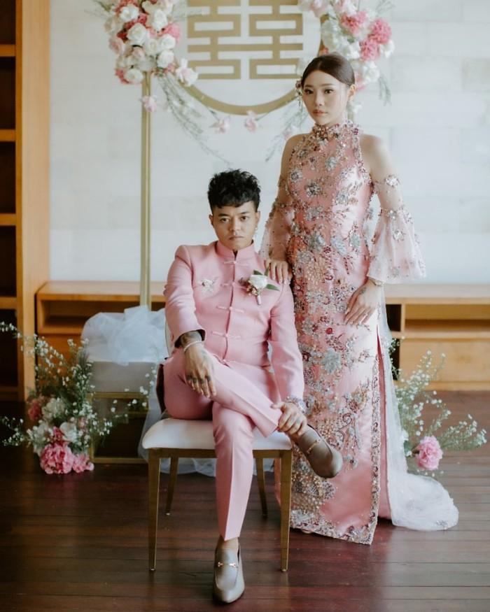 Ini dia penampilan Reza dan Wendy dalam prosesi Tea Pai. Kompak mengenakan busana khas Tionghoa bernuansa soft pink, gaun Wendy yang bermodel halterneck tampak elegan dengan detail payet dan lengan lonceng. (Foto: instagram.com/baliweddingspecialist)