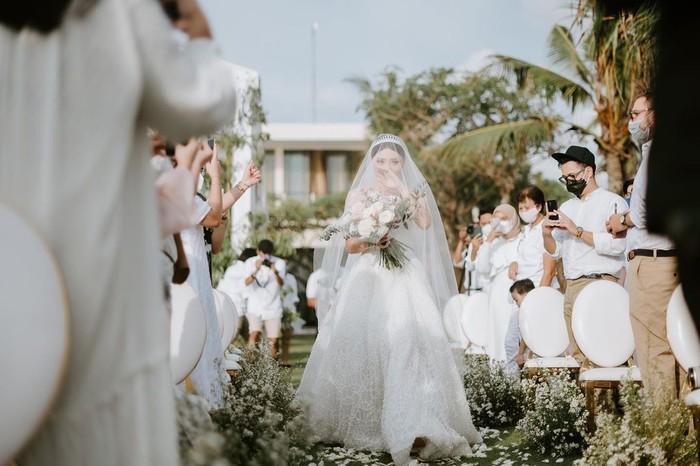 Sementara untuk resepsi, Wendy mengenakan gaun modern berwarna putih lengkap dengan kain veil yang menutupi wajah dan menjuntai indah ke belakang. Gaun yang dikenakannya ini merupakan rancangan dari desainer Cynthia Tan. (Foto: instagram.com/wendywalters)